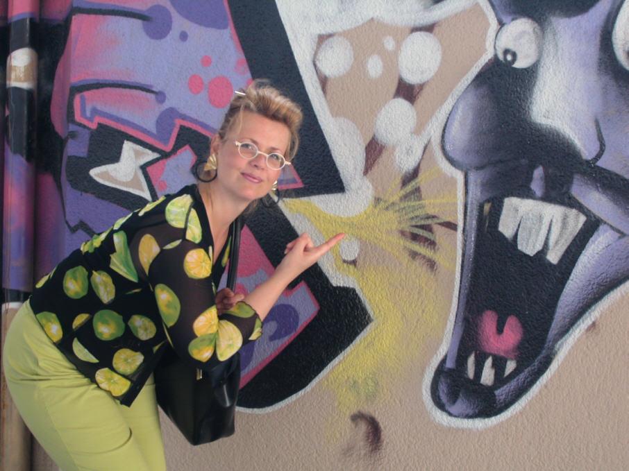 Andra von Avalon vor einer Graffitti mit einem lachenden Cartoon-Gesicht